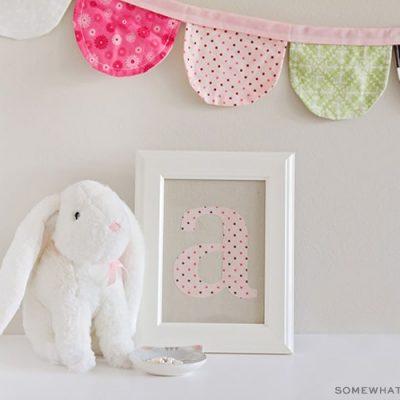 framed fabric monogram next to a stuffed bunny