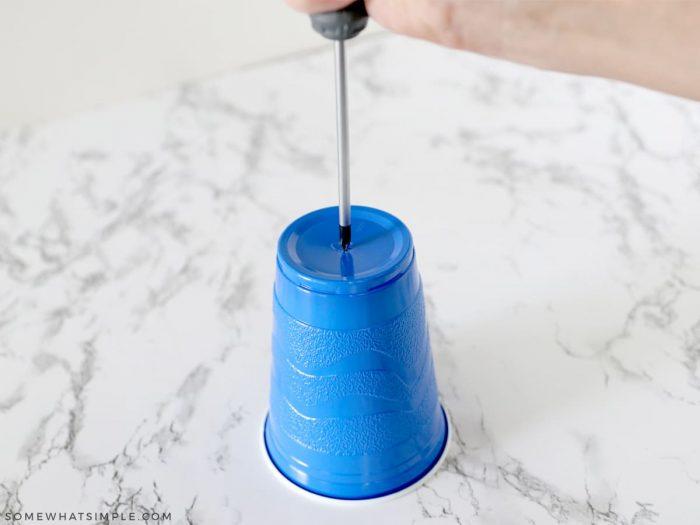screwdriver puncturing plastic cup