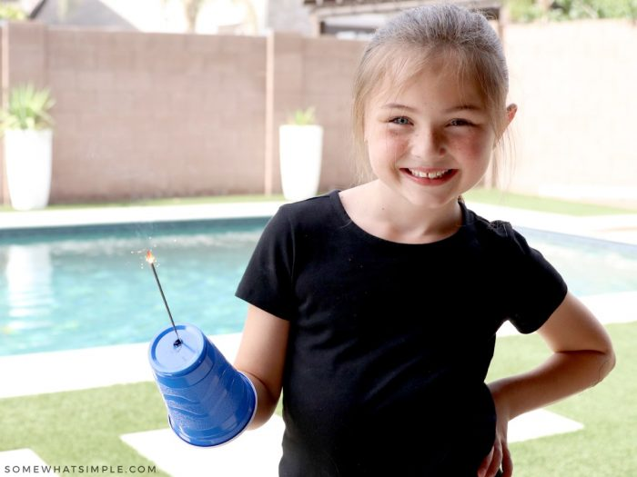 little girl holding a cup with a sparkler