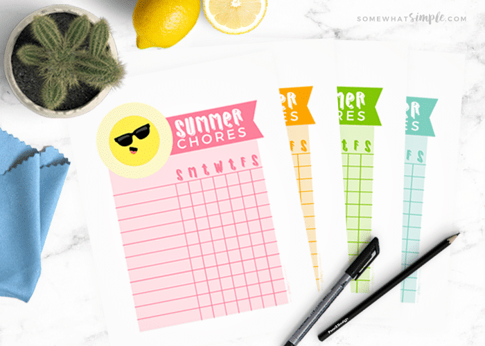 summer chore charts next to some pens on a white counter